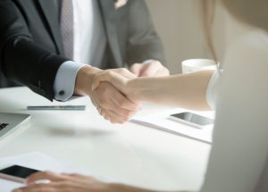 Closeup of male and female hands handshaking after effective negotiation showing mutual respect and intention for strong working relationships. Man in suit greeting female partner. Business concept